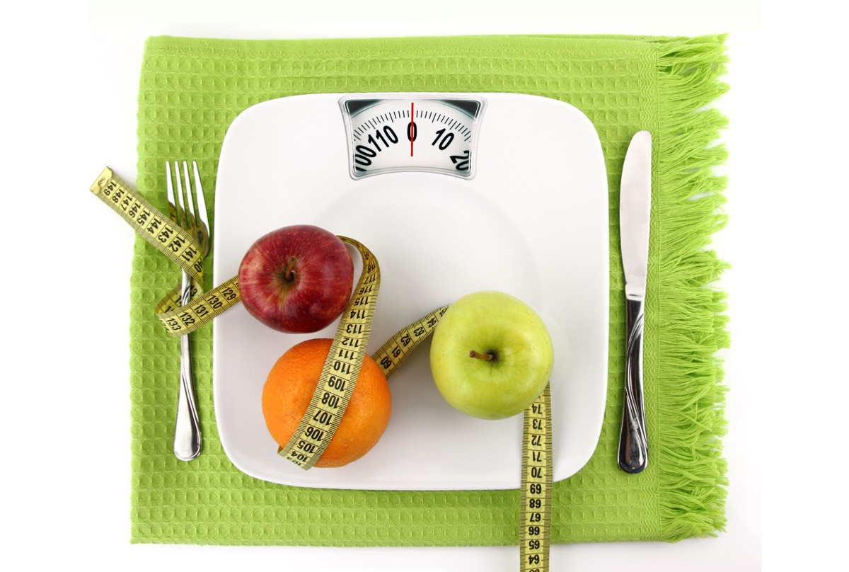 Scales representing a dinner plate with fruit and tape measure to represent weight loss